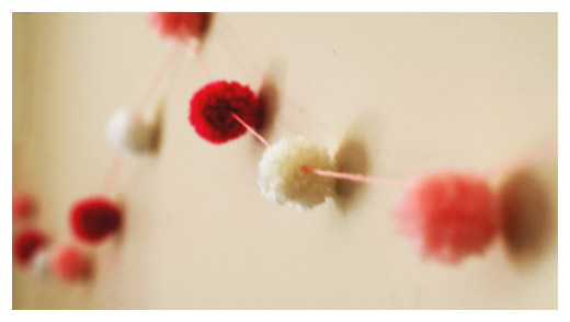 pompom garland hanging on wall
